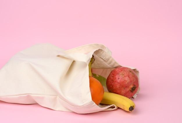 Bolsa textil beige con frutas frescas sobre fondo rosa, cero residuos