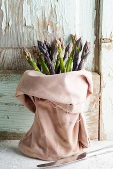 Bolsa de textil con manojo de espárragos orgánicos naturales frescos contra la pared de madera vieja.