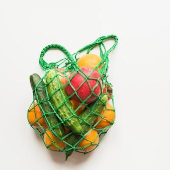 Bolsa textil verde con productos.