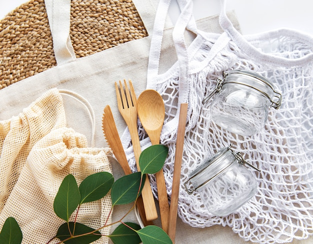 Bolsas de algodón, bolsa de red con tarros de vidrio reutilizables y cubiertos de bambú. concepto de desperdicio cero. respetuoso del medio ambiente. endecha plana