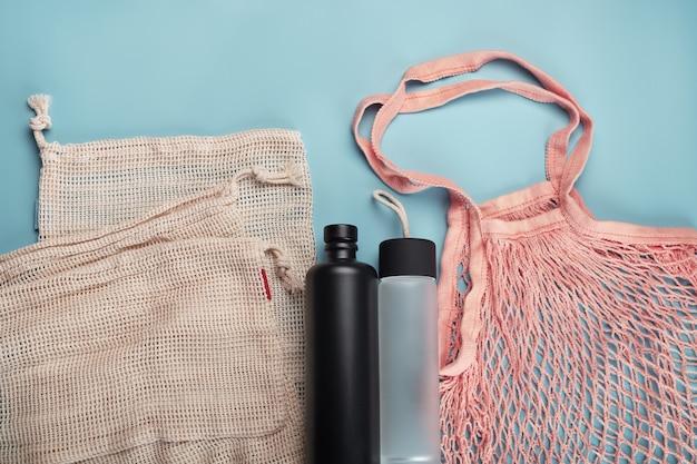 Bolsas ecológicas de algodón y botellas de agua en azul