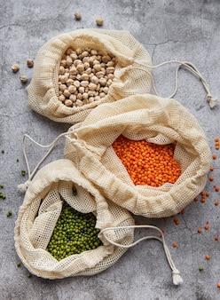 Bolsas ecológicas con diferentes tipos de legumbres en un escritorio de hormigón