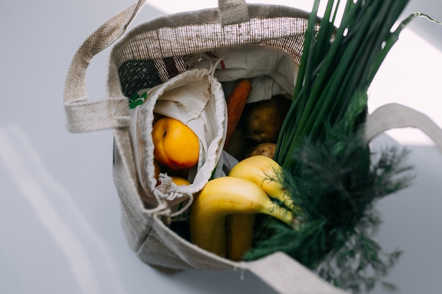 Bolsas ecológicas con frutas y verduras frescas.