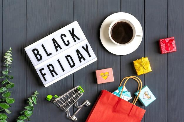 Bolsas de embalaje multicolores, carretilla, ramita de eucalipto, taza de café cajas de regalo caja de luz con texto black friday en superficie gris oscuro