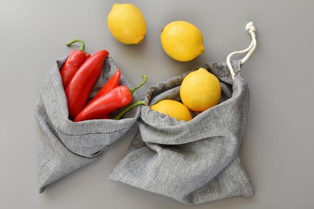 Bolsas de lino reutilizables con limones y pimiento rojo, estilo de vida sin desperdicio.