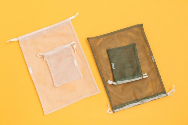 Bolsas de malla reutilizables para la compra de comestibles llenas en la pared amarilla.