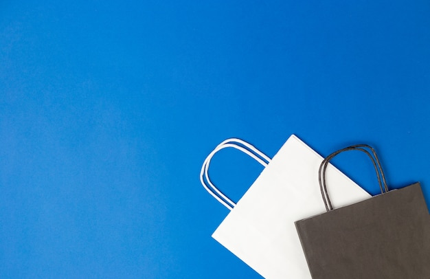 Bolsas de papel blanco y negro con asas en pared azul