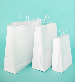 Bolsas de papel blanco sobre fondo azul.