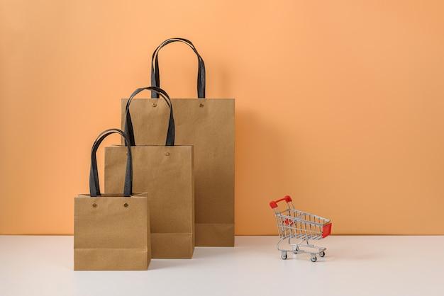 Bolsas de papel y carrito de compras o carro en mesa blanca y pared de color naranja pastel