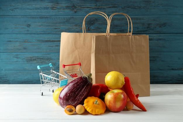 Bolsas de papel, carros de compras, verduras y frutas en mesa de madera