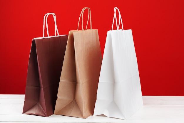 Bolsas de papel con copia espacio sobre fondo rojo.