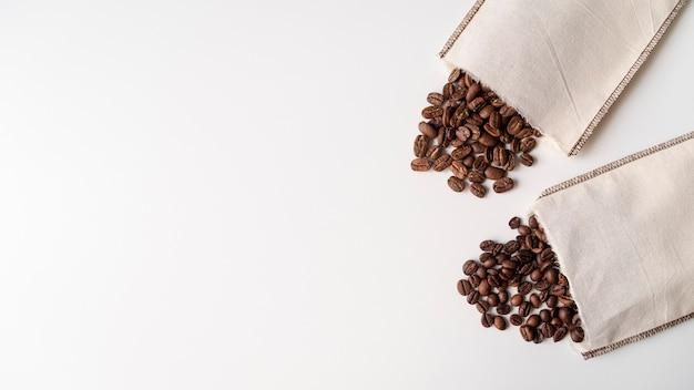 Bolsas de papel con granos de café de superficie blanca