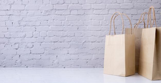 Bolsas de papel kraft con espacio de copia sobre fondo de textura de pared de ladrillo.