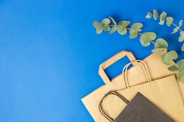 Bolsas de papel negro y marrón con asas y hojas de eucalipto sobre superficie azul