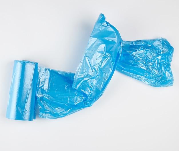 Bolsas de plástico azul retorcidas para bin sobre fondo blanco.