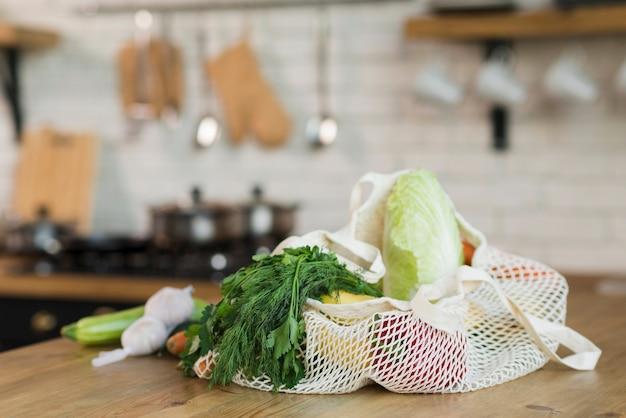 Bolsas reutilizables de primer plano con comestibles orgánicos en la mesa