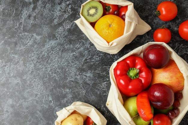 Bolsas con verduras y frutas sobre mesa ahumada negra