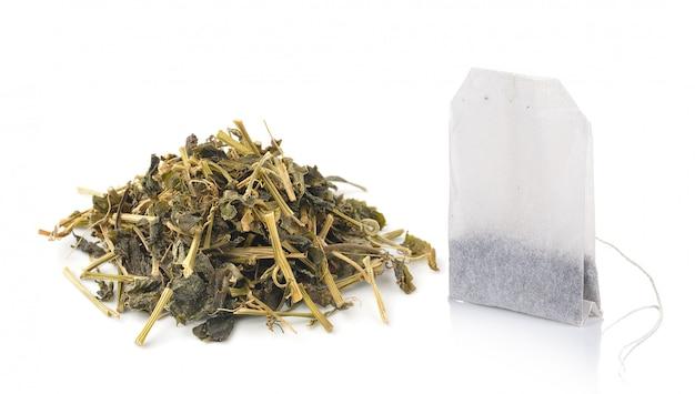 Bolsita de té y té seco aislado sobre fondo blanco.