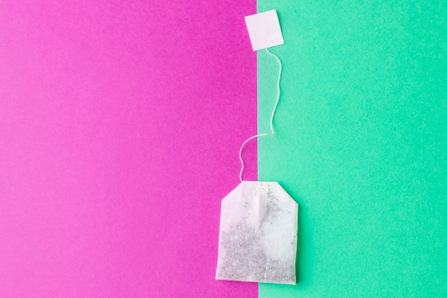 Bolsitas de té con etiquetas blancas sobre un fondo verde pastel y rosa brillante
