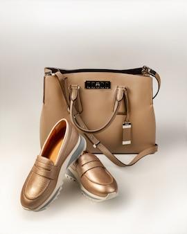 Bolso beige y un par de zapatos de oro rosa