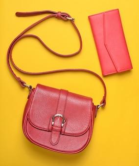 Bolso y bolso de cuero rojo para mujer sobre fondo amarillo pastel, accesorios para mujer, vista superior, minimalismo