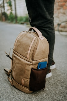 Bolso para cámara de lona marrón con un teléfono inteligente en el bolsillo lateral, en el suelo