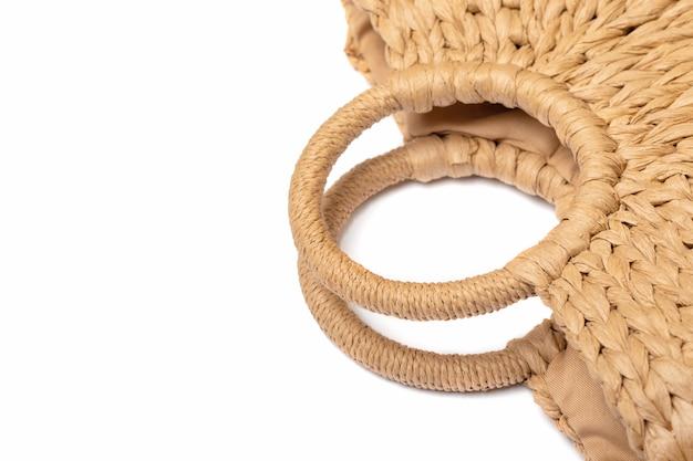 Bolso de la cesta de paja de mimbre aislado en la pared blanca. bolsa de verano de playa u otoño vintage en detalle