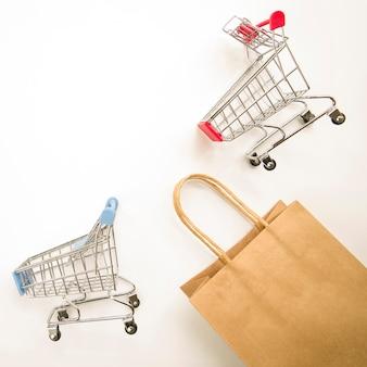 Bolso de compras artesanal cerca de carritos de supermercado.