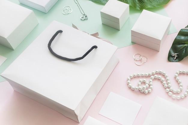 Bolso de compras blanco y cajas de regalo con joyas en colores de fondo