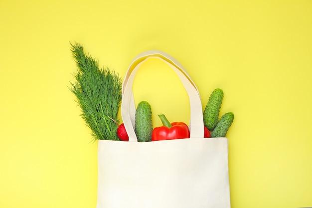 Bolso de compras del eco del algodón con las verduras en fondo amarillo visión superior, espacio de la copia.