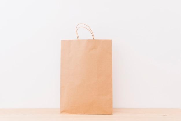 Bolso de compras marrón en superficie de madera