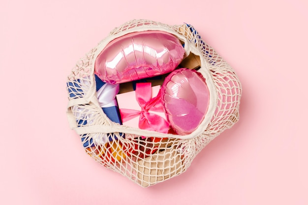 Bolso de compras con regalo y globo en forma de corazón sobre una superficie rosa. concepto de regalos para la familia, seres queridos, navidad, día de san valentín. . vista plana, vista superior