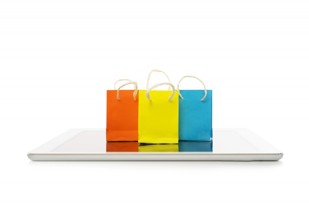 Bolso de compras con la tableta en el fondo blanco, las compras en línea o el concepto de comercio electrónico