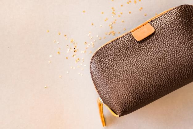 Bolso cosmético marrón sobre fondo beige brillante. concepto de belleza diseño plano laico.