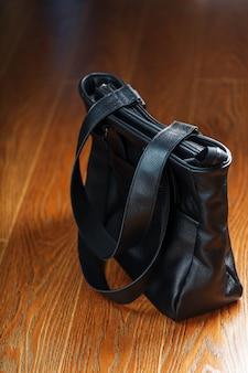 Bolso de cuero negro hecho a mano sobre un fondo de madera, hecho de material natural.