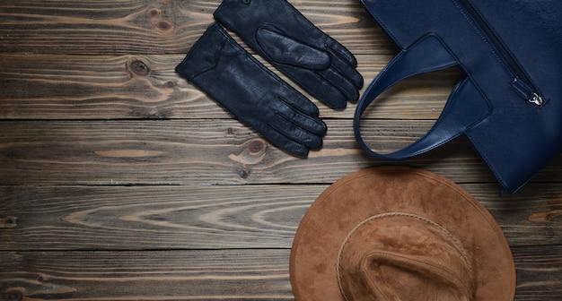 Bolso de cuero, sombrero de fieltro, guantes sobre un fondo de madera. accesorios de mujer. colección de otoño. vista superior. copia espacio