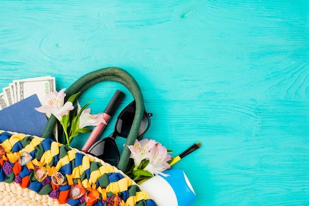 Bolso con dinero entre flores cerca de lentes de sol y pintalabios.