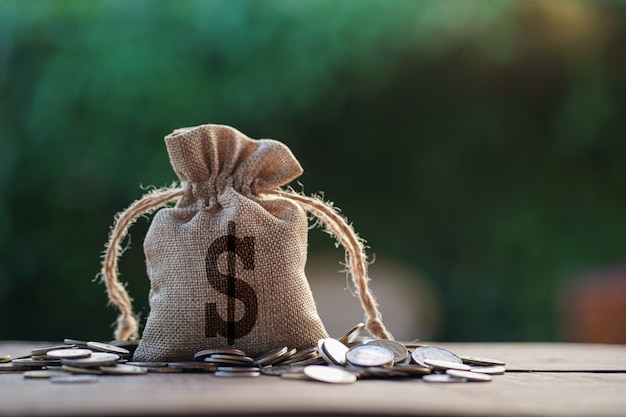 Bolso del dinero en la madera con la pila de las monedas en luz de la mañana.