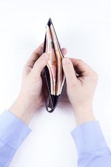 Bolso con dinero en las manos.