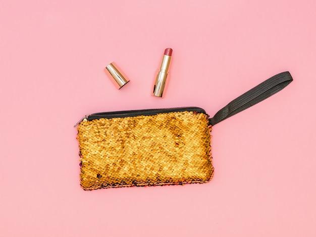 Bolso dorado de mujer con lápiz labial abierto sobre mesa rosa. color pastel. lay flat.