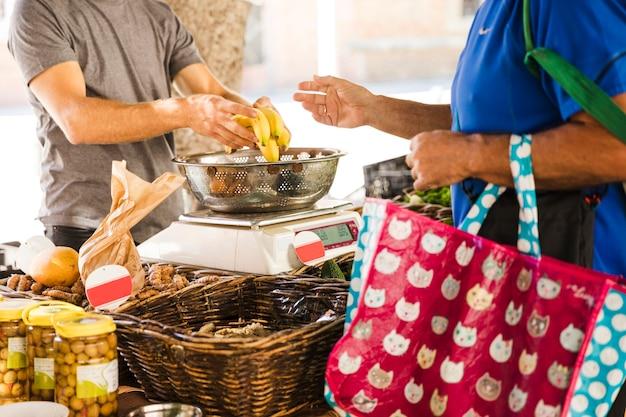 Bolso de la explotación agrícola del hombre que compra plátanos del vendedor de la fruta en mercado