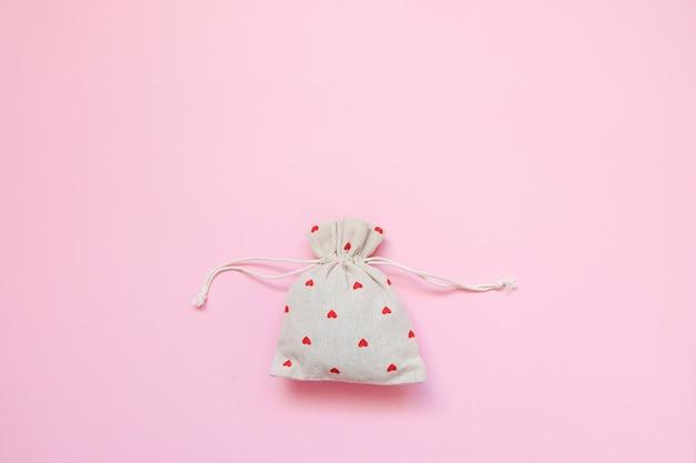 Bolso de lino con corazones rojos sobre fondo rosa.