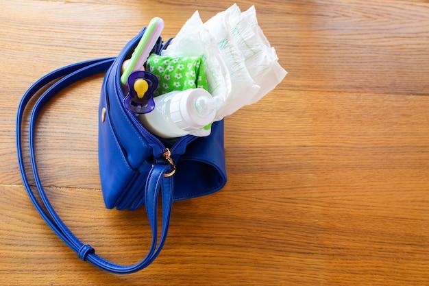 Bolso de mujer con artículos para el cuidado del niño.