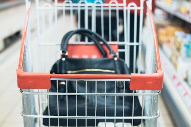 Bolso de la mujer en el carro en un supermercado