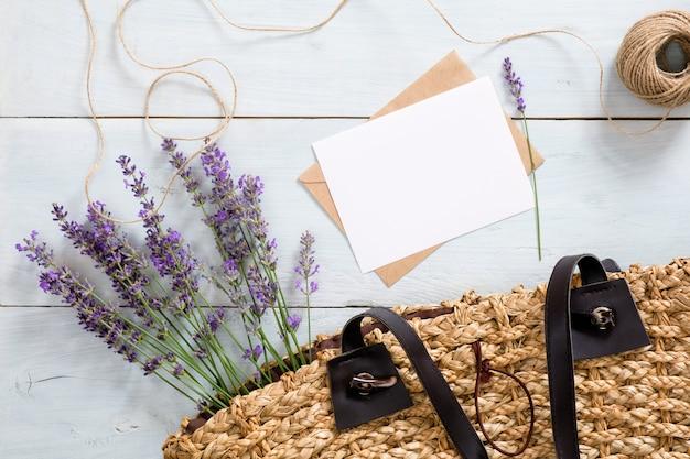 Bolso de mujer con flores de lavanda, tarjeta de papel en blanco y sobre en el escritorio de madera azul