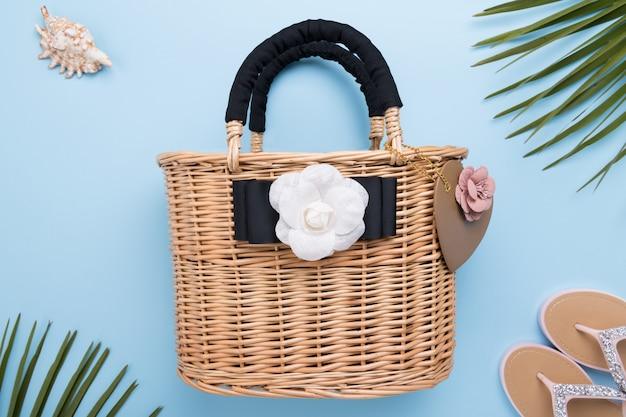 Bolso de mujer de moda de mimbre en superficie azul pastel claro, primer plano, concepto de viajes y vacaciones, vista superior, concepto de verano