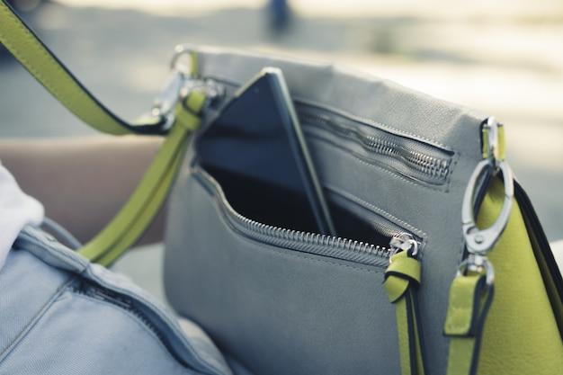 Bolso de mujer con el teléfono en la calle de cerca