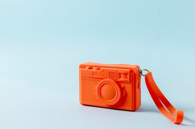 Un bolso naranja con cremallera sobre fondo azul.