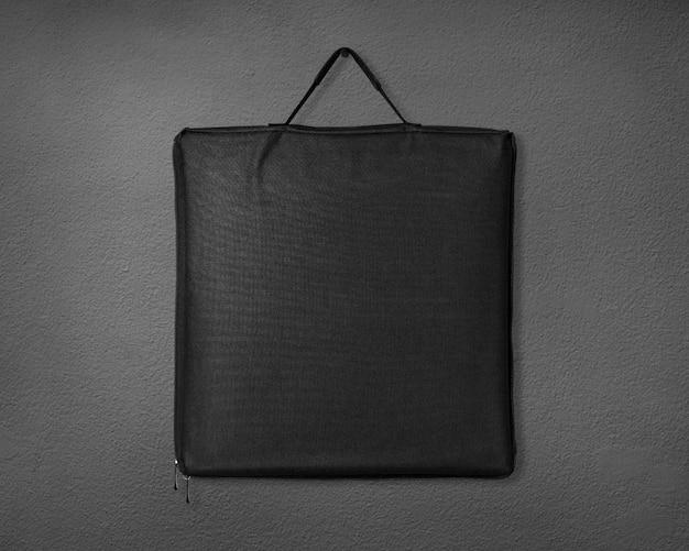 Bolso negro de la tela en fondo del cemento.