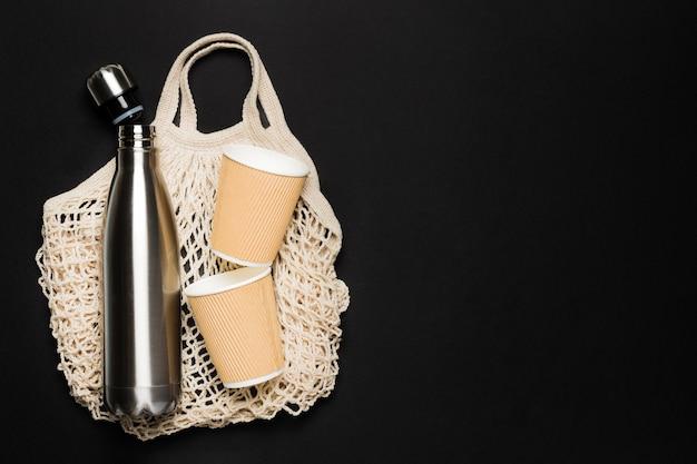 Bolso con objetos ecológicos sobre fondo negro